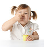 A menina engraçada come o yogurt Fotografia de Stock