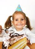 Menina engraçada da criança com chapéu do aniversário que come o bolo Foto de Stock