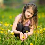Menina engraçada nos fones de ouvido no campo verde feliz Foto de Stock