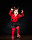 Menina engraçada pequena no traje do joaninha Imagem de Stock