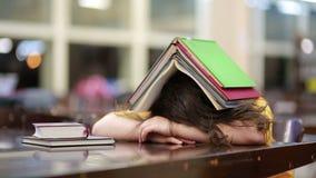Menina enterrada sob a pilha de livro video estoque