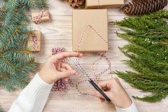 A menina entrega o envolvimento do presente do ano novo, processo do papel de embrulho, bordado, faculdade criadora Foto de Stock Royalty Free