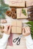 A menina entrega o envolvimento do presente do ano novo, processo do papel de embrulho, bordado, faculdade criadora Fotos de Stock Royalty Free