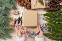 A menina entrega o envolvimento do presente do ano novo, processo do papel de embrulho, bordado, faculdade criadora Fotos de Stock