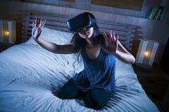 A menina entusiasmado e feliz atrativa nova que veste os auriculares do jogo da realidade virtual de VR que jogam a apreciação su foto de stock