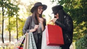 A menina entusiasmado está olhando suas compras do ` s do amigo nos sacos, fazendo perguntas sobre preços e coleções e expressar video estoque