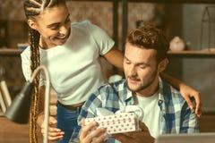 Menina entusiasmado que dá a seu noivo presente inesperado fotos de stock royalty free