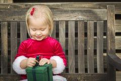 Menina entusiasmado que desempacota seu presente em um banco fotos de stock royalty free
