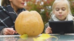 Menina entusiasmado que procura ideias da jaque-o-lanterna na tabuleta, mamã que cinzela a abóbora video estoque