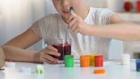 Menina entusiasmado que toma o ovo colorido do vidro com coloração de alimento vermelha, mágica da Páscoa vídeos de arquivo