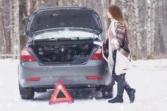 Menina envolvida em uma cobertura colocada perto do carro quebrado fotografia de stock