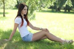 Menina erótica com a mini saia na grama verde fotografia de stock royalty free