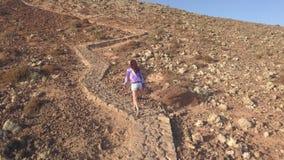 A menina escala acima uma inclinação de uma montanha filme