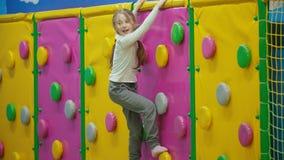 A menina escala a parede de escalada