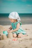 A menina escava furos na areia na praia Foto de Stock
