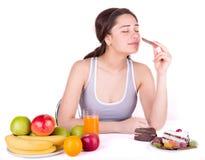 A menina escolhe entre doces e frutos fotos de stock royalty free