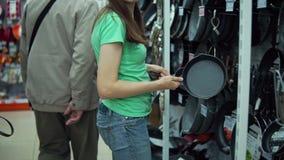 A menina escolhe a frigideira na loja filme