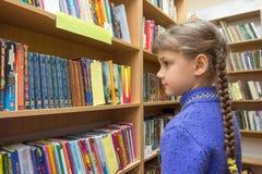 A menina escolhe livros na biblioteca fotos de stock