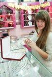 A menina escolhe o anel na loja Imagens de Stock