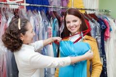 A menina escolhe o vestido de noite na loja de roupa Imagens de Stock Royalty Free