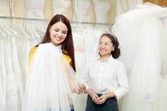 A menina escolhe o véu nupcial na loja da forma do casamento Fotografia de Stock