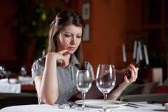 A menina escolhe a refeição no restaurante fotografia de stock