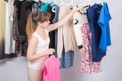A menina escolhe a roupa imagens de stock
