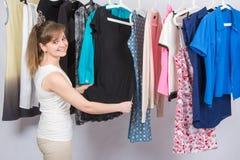 A menina escolhe a roupa e com o sorriso, olhado no quadro imagem de stock royalty free
