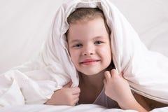 A menina escondeu sua cabeça sob uma cobertura branca, olhou e sorriu imagem de stock