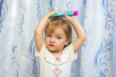 A menina escova o cabelo com uma escova de cabelo Fotografia de Stock
