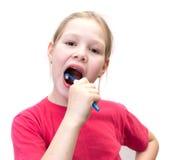 A menina escova os dentes uma escova Foto de Stock