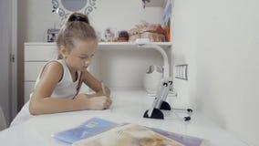 A menina escreve aos escrita-livros A decisão das lições trabalhe com PC da tabuleta em casa e fazendo trabalhos de casa vídeos de arquivo
