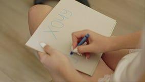 A menina escreve corrige dentro em uma folha do cartão Fim acima Jogo Em um bom modo filme