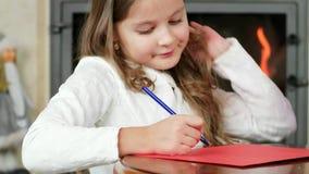 A menina escreve, a criança tira a pena na folha de papel, menina bonito que senta-se perto da chaminé em onde o fogo se está que video estoque