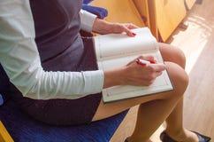 A menina escreve em um caderno Fotos de Stock Royalty Free