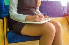 A menina escreve em um caderno Imagem de Stock Royalty Free