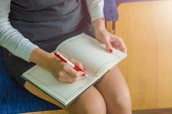 A menina escreve em um caderno Imagens de Stock