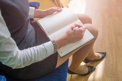 A menina escreve em um caderno Foto de Stock Royalty Free