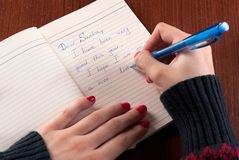 A menina escreve a letra a Santa Claus na mesa de madeira imagem de stock