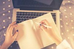 A menina escreve no caderno Imagem de Stock