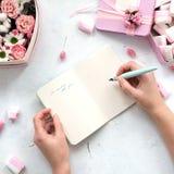 A menina escreve no caderno aberto na tabela com flores e marshmallows, cores pastel Configuração lisa da beleza Copie o espaço O fotos de stock royalty free