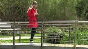 A menina escreve no telefone na rua filme