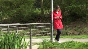 A menina escreve no telefone na rua video estoque