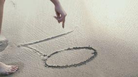 A menina escreve o amor da palavra na areia molhada video estoque