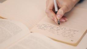 A menina escreve para baixo algo de um livro que senta-se na tabela em uma biblioteca vídeos de arquivo