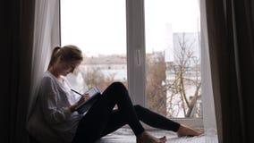 A menina escreve suas memórias em um caderno vídeos de arquivo