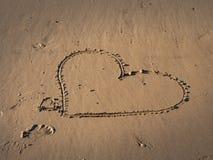 A menina escreve um símbolo do coração na areia em uma praia fotografia de stock royalty free