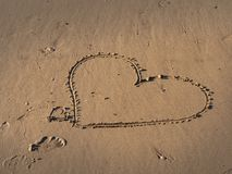 A menina escreve um símbolo do coração na areia em uma praia foto de stock