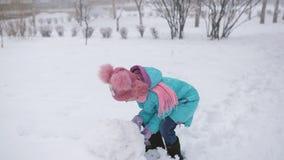 A menina esculpe um boneco de neve no inverno fora da neve vídeos de arquivo