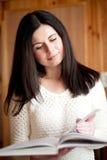 a menina Escuro-de cabelo lê o livro Fotos de Stock